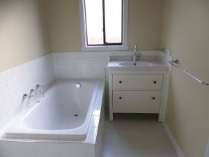 Renovated bathroom with new vanity unit and bath tub